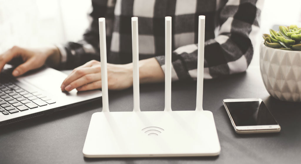 girl-works-at-laptop-with-router-on-table